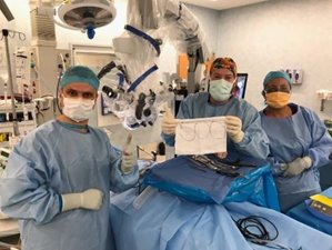 Dr Bart De Boer holds a '500'th case sign in surgical gowns with two other colleagues